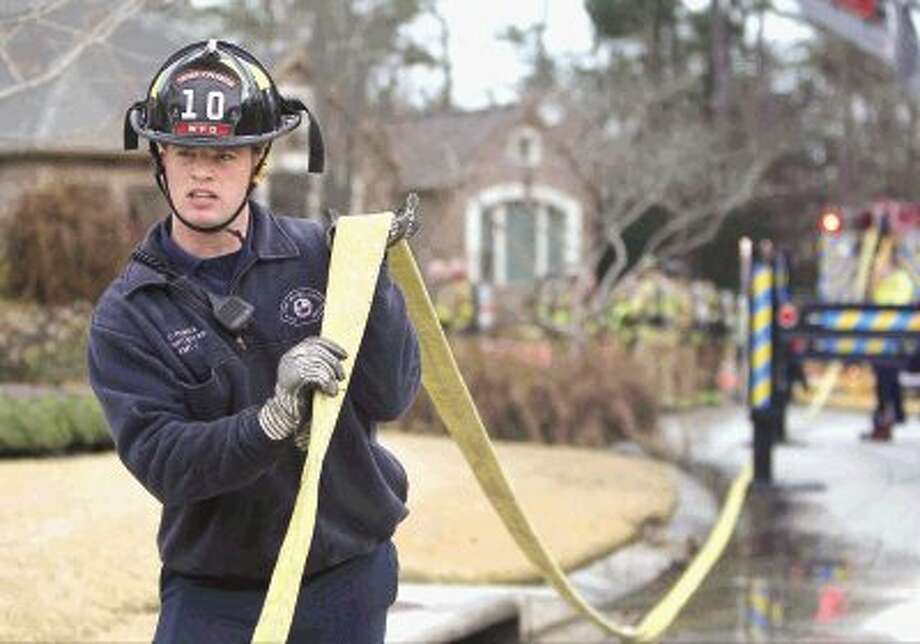 The Woodlands firefighter Chris Polnick helps put up a firehose at the scene of a house fire on N. Emory Bend Place Wednesday. Photo: Staff Photo By Jason Fochtman