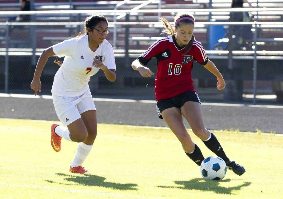 Porter's Kenady Carlile dribbles past Caney Creek's Mercedes Garcia during a soccer match Friday. Photo: Jason Fochtman