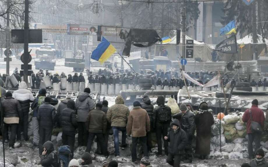 Protesters guard the barricades in front of riot police in Kiev, Ukraine, Wednesday, Jan. 29, 2014. Ukraine's parliament is considering measures to grant amnesty to those arrested during weeks of protests in the crisis-torn country, but possibly with conditions attached that would be unacceptable to the opposition. Photo: Efrem Lukatsky