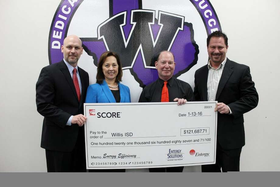 Willis ISD superintendent Tim Harkrider accepts a check for $121,687.71 from Entergy for energy efficiency program participation. He stands with Sallie Rainer, president and chief executive officer, Entergy Texas, Inc.; Paul Dusebout, executive director, Willis ISD support services; and Phil Lanier, account manager, Entergy Texas, Inc at the school board meeting Wednesday.