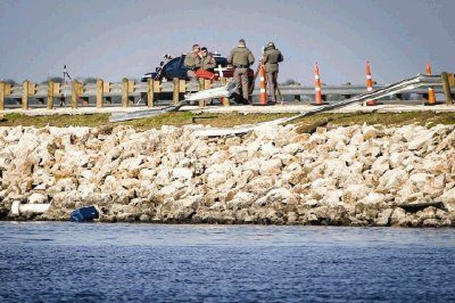 Emergency responders secure the scene where a truck crashed through the guard rail of the FM 1097 bridge over Lake Conroe Sunday morning. Photo: Michael Minasi