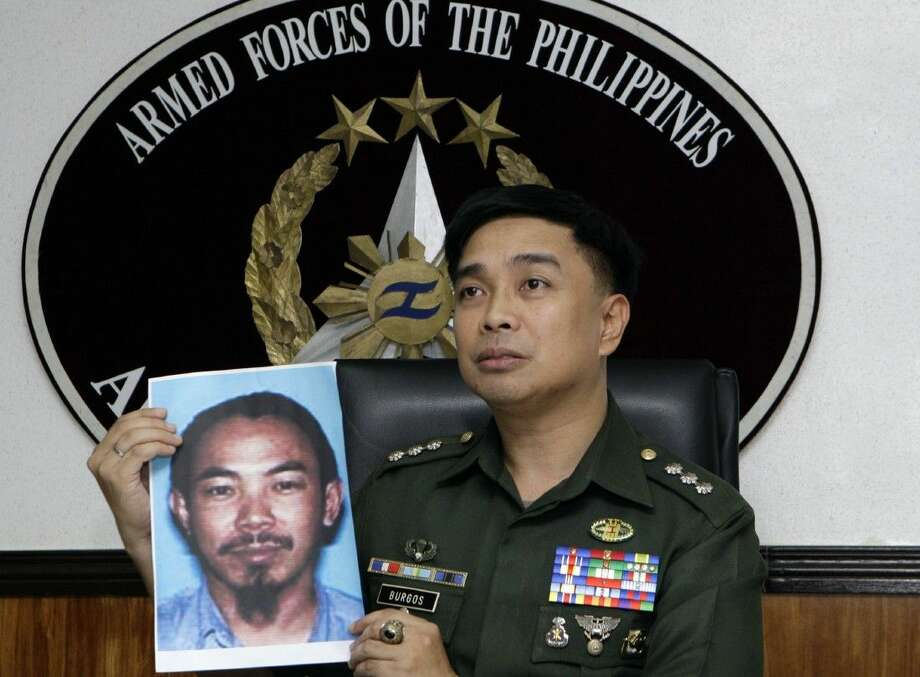 Then-Armed Forces of the Philippines spokesman Col. Marcelo Burgos shows a picture of Malaysian Zulkifli bin Hir, also known as Marwan, during a press conference Feb. 2, 2012, in suburban Quezon City, north of Manila, Philippines.