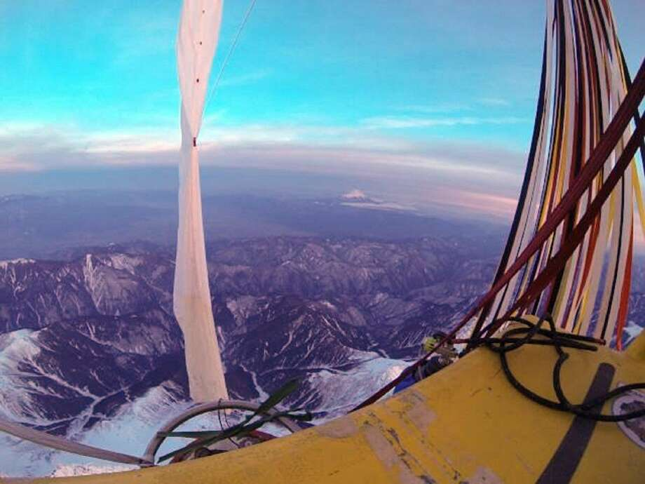 The helium-filled balloon carrying Troy Bradley and Leonid Tiukhtyaev passes over Mt. Fuji on Monday. The two pilots landed safely off the coast of Mexico early Saturday after an audacious, nearly 7,000-mile trip across the Pacific Ocean that shattered two long-standing records for ballooning. Photo: HONS