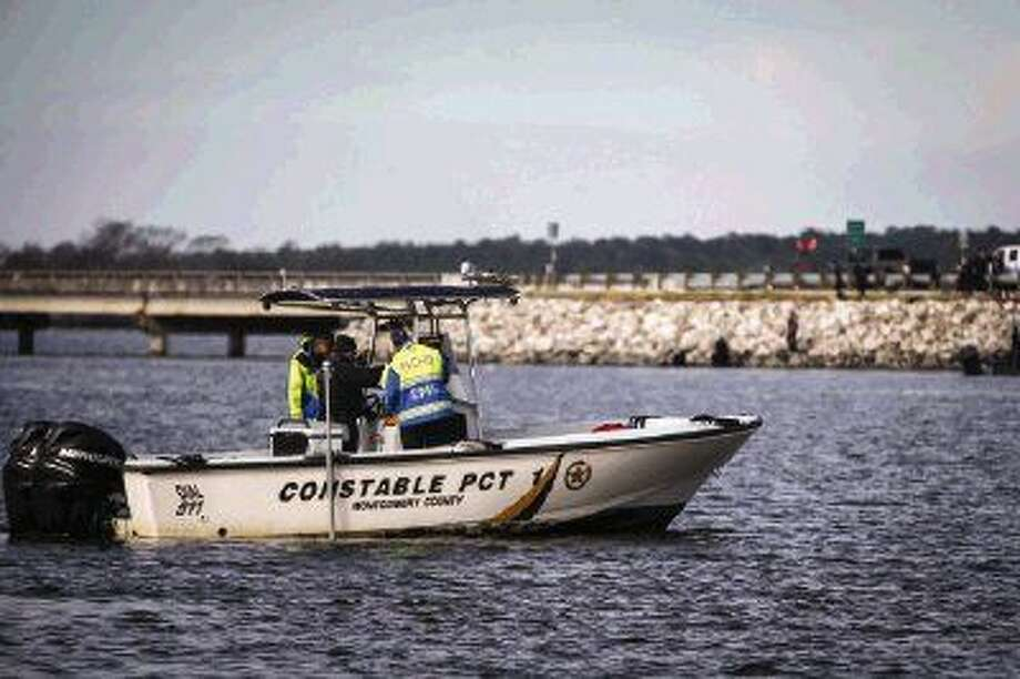 Montgomery County Precinct 1 constables search Lake Conroe near the FM 1097 bridge on Monday for a man who went missing after a truck crashed through a guard rail on the bridge into the lake early Sunday morning.