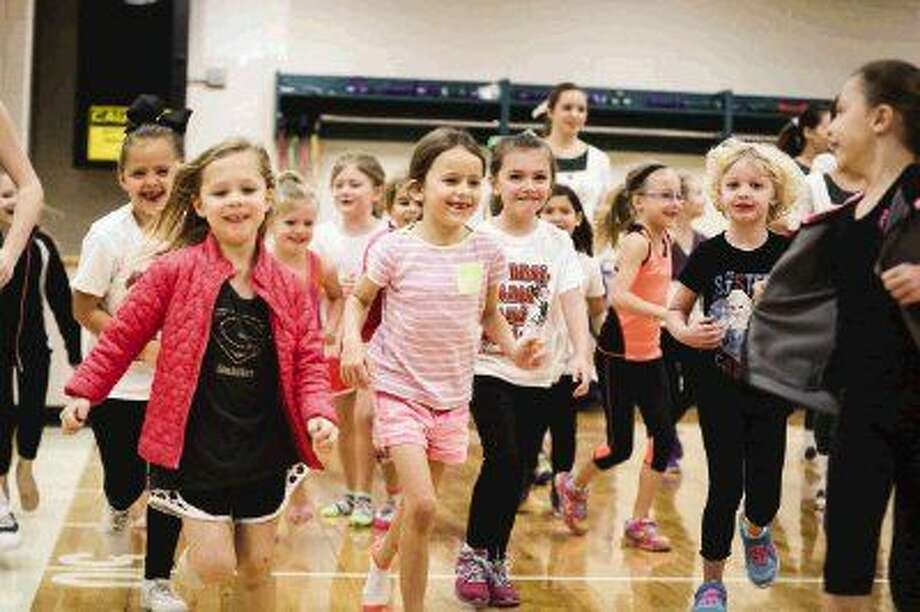 Students in a classes ranging from Kindergarten to second grade warmup with a run during The Woodlands Highsteppers' annual Winter/Spring Dance Clinic on Saturday at The Woodlands High School 9th Grade Campus.