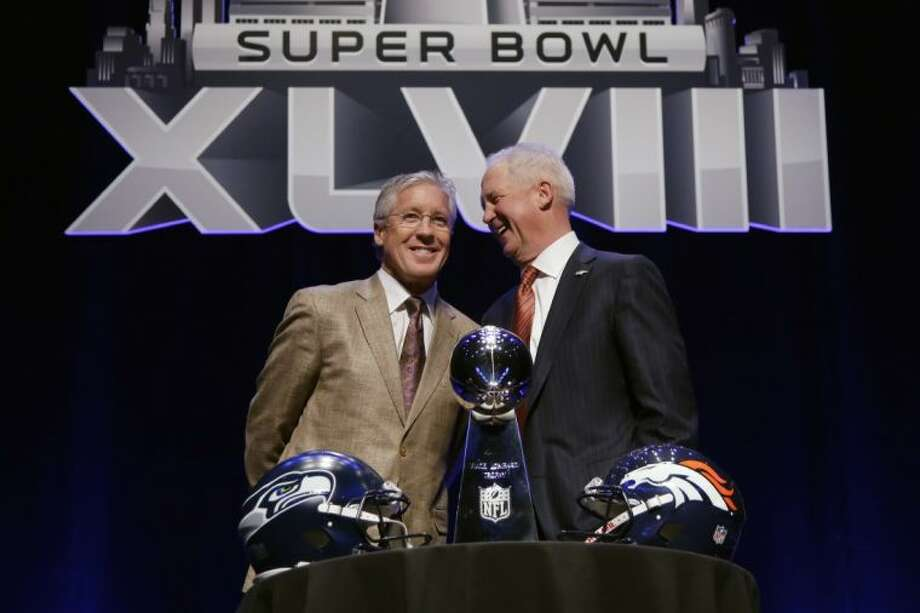 Seahawks coach Pete Carroll, left, and the Broncos' John Fox share a laugh before Super Bowl XLVIII. Photo: Matt Slocum