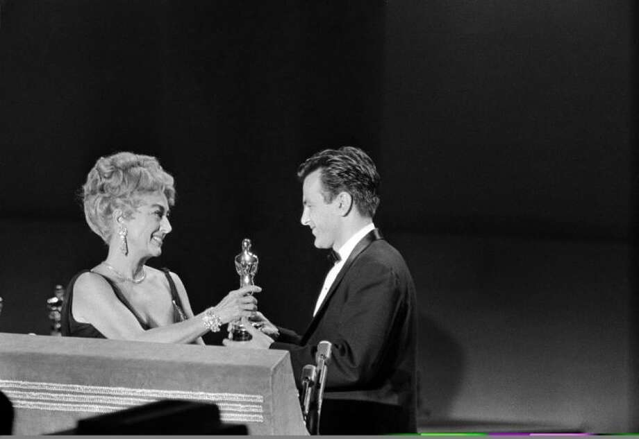 "In this April 9, 1962 file picture Joan Crawford, acting as presenter for the Academy of Motion Picture Arts and Sciences, presents an Oscar to Maximilian Schell on the stage at Santa Monica, Calif., April 9, 1962, after he was named as best actor of the year for his performance in ""Judgment at Nuremberg."""