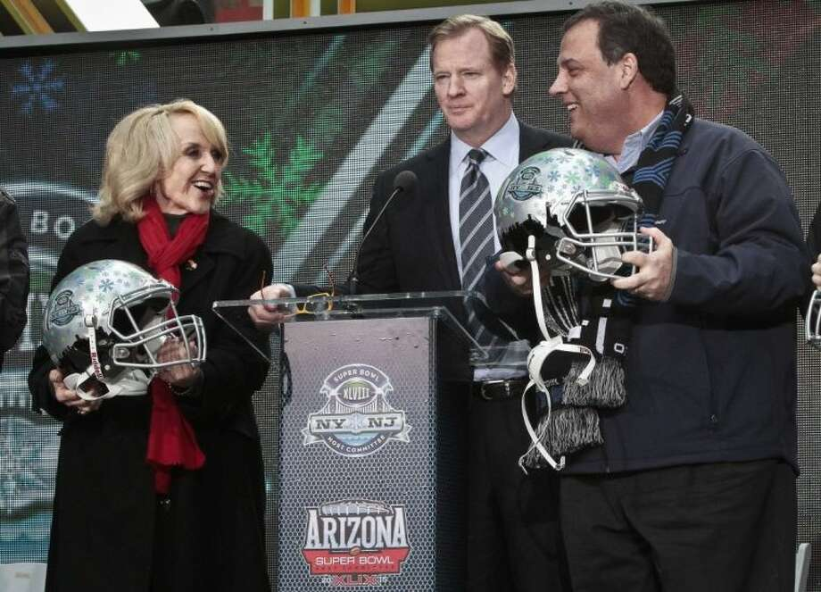 NFL Commissioner Roger Goodell, center, stands between Arizona Gov. Jan Brewer, left, and New Jersey Gov. Chris Christie, right, showoff souvenir football helmets after a ceremony to pass official hosting duties of next year's Super Bowl to Arizona, Saturday Feb. 1, 2014 in New York. Photo: Bebeto Matthews