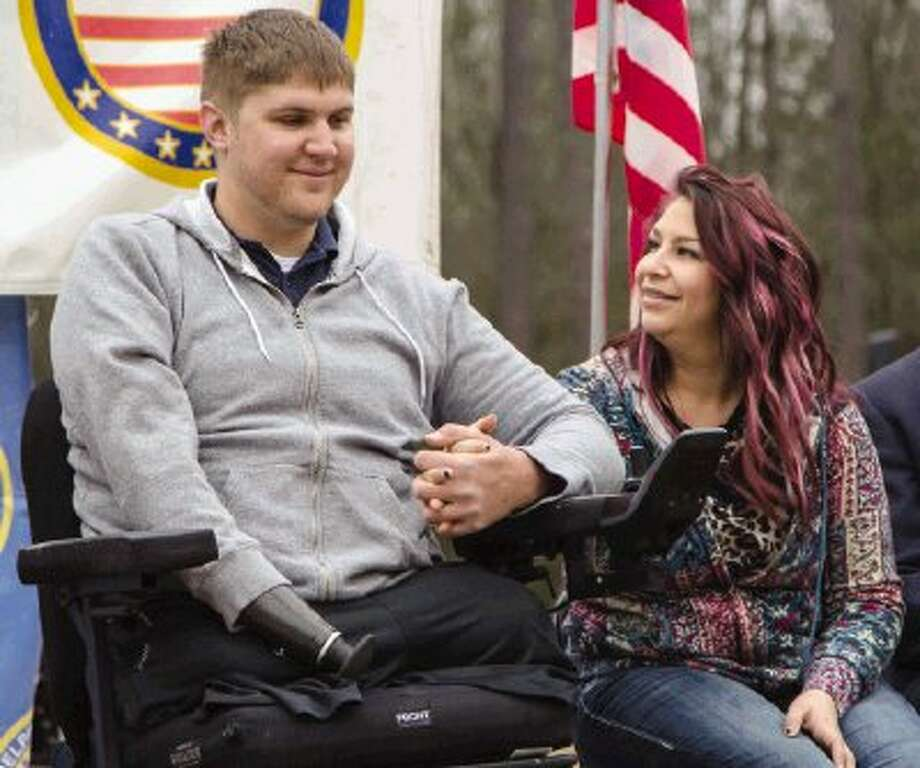 Sgt. Ben Eberle and his wife Ashley hold hands during a groundbreaking ceremony on the property for a home being built for him and his family Monday in Montgomery. Eberle is a triple amputee after losing his legs and right hand during an improvised explosive device (IED) explosion in Afghanistan. Children from Kids R Kids and members of The Woodlands High School Band and TWHS Jr. ROTC performed during the event hosted by Helping a Hero Program. To view or purchase this photo and others like it, visit HCNpics.com. / The Conroe Courier/ The Woodland