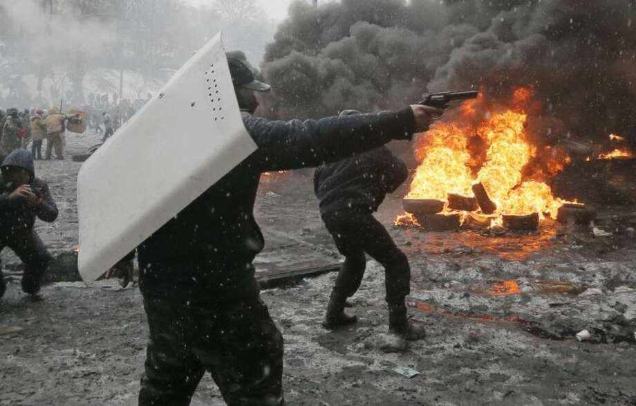 A protester points a handgun during a clash with police in central Kiev, Ukraine Jan. 22. After two months of anti-government protests, modern Ukraine has never been so bitterly polarized. To be sure, Ukraine has long been divided. Russia and Europe have vied for dominance for centuries, causing deep cultural differences between the mostly Ukrainian-speaking western and central regions on the one hand, and the Russian-speaking east and south on the other. But as the crisis has deepened, each side has grown stronger in its convictions, and those who stood in the middle have been forced to choose sides. Photo: Efrem Lukatsky