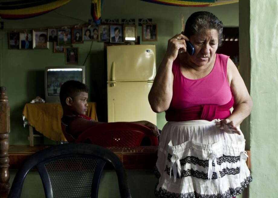 Maria Alvarenga, mother of the Jose Salvador Alvarenga talks by cell phone, at of her house in the village Garita Palmera, El Salvador, Tuesday. The account of her son's survival after more than 13 months in an open boat has proven a double miracle for his family, who lost touch with him years ago and thought he was dead. Alvarenga says he left Mexico early 2012 for a day of shark fishing and ended up on the remote Marshall Islands. Photo: Esteban Felix