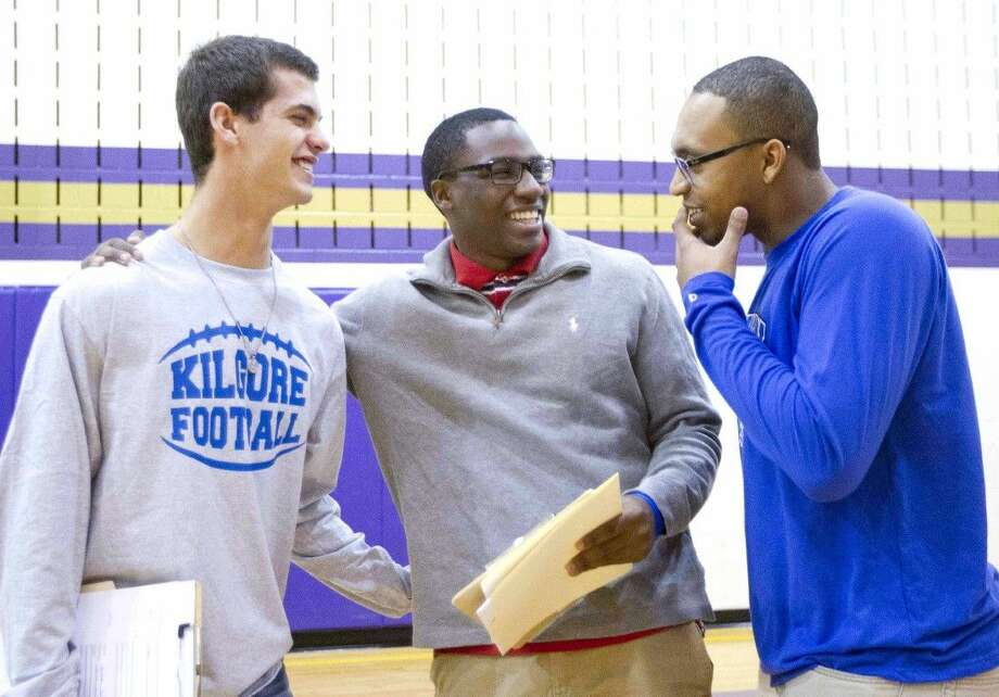 Paul Allen, center, jokes with Josh Bolfing, left, and Johnathan Thomas during a National Signing Day ceremony Wednesday. To view or purchase this photo and others like it, visit HCNpics.com. Photo: Jason Fochtman