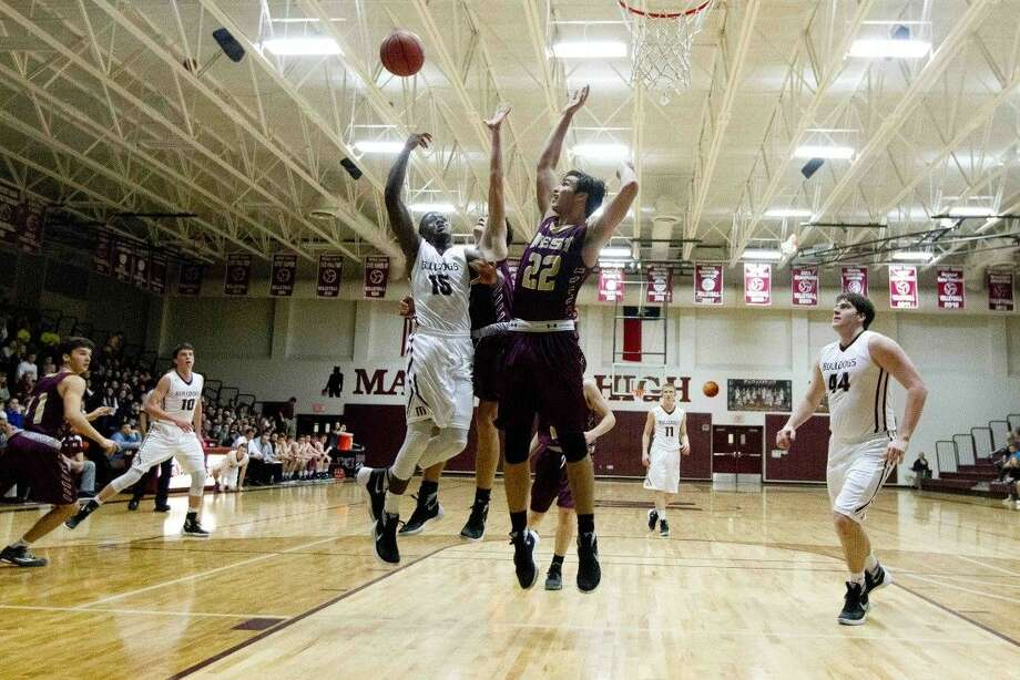 Magnolia guard Michael Woods is fouled by going up for a shot as Magnolia West power forward Colin Just applies pressure this past Friday night. Photo: Jason Fochtman