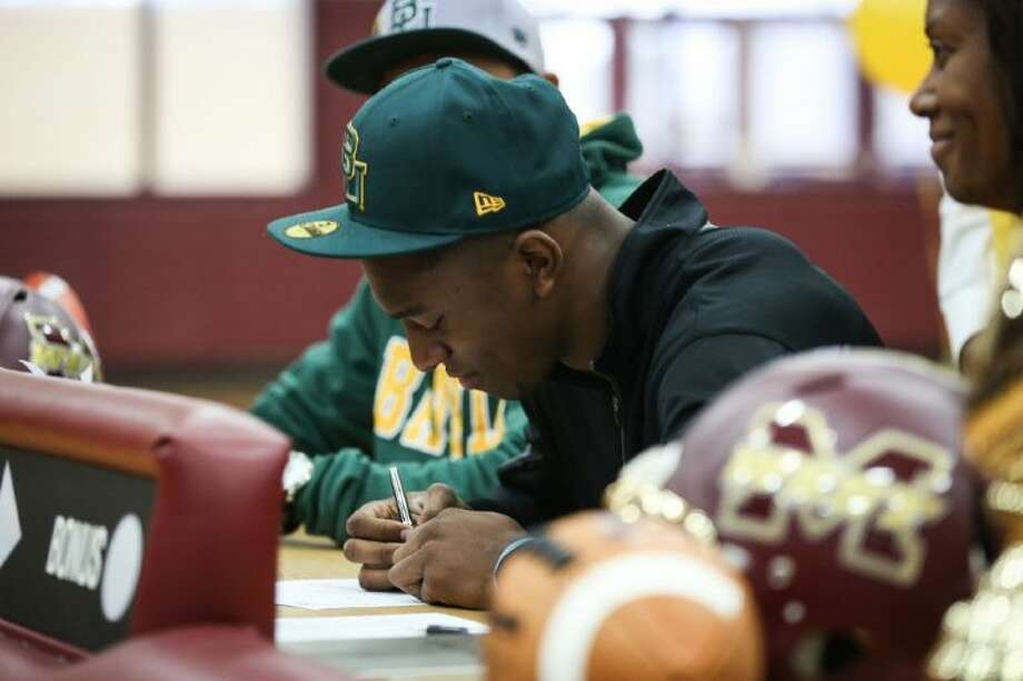 Magnolia West football player Xavier Jones signs a national letter of intent with Baylor University during a ceremony on Wednesday at Magnolia West High School. Photo: Michael Minasi