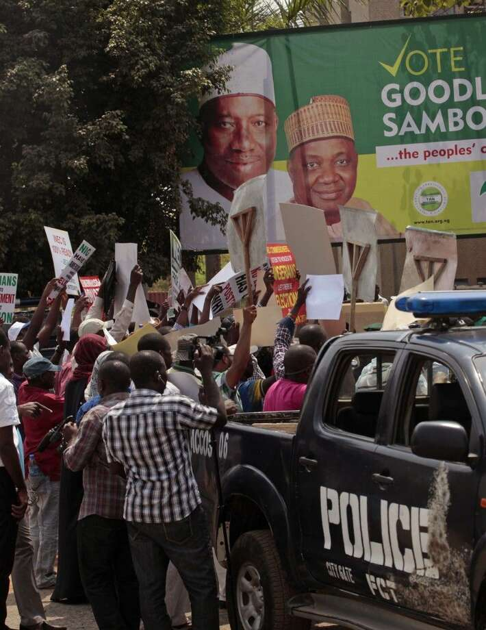 Demonstrators hold banners during a protest against the possible postponement of elections Saturday in Abuja, Nigeria. Photo: Lekan Oyekanmi