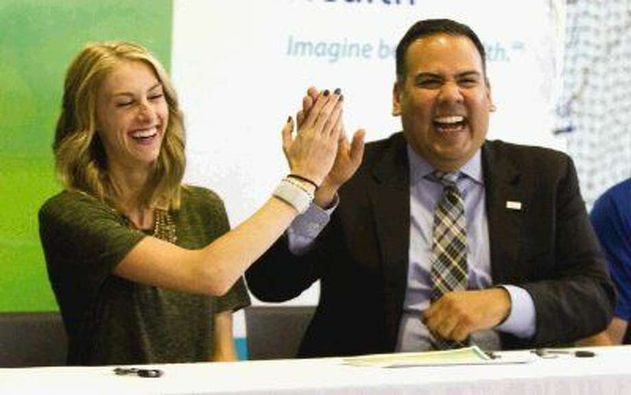 Samantha McClellan, left, gives David Argueta, president and CEO of Chi St. Luke's Health - The Woodlands, a high-five after signing a letter of committment Tuesday. McClellan plans to compete for one of three female slots in the 2016 Rio Olympic marathon trial in Los Angeles Feb. 13.