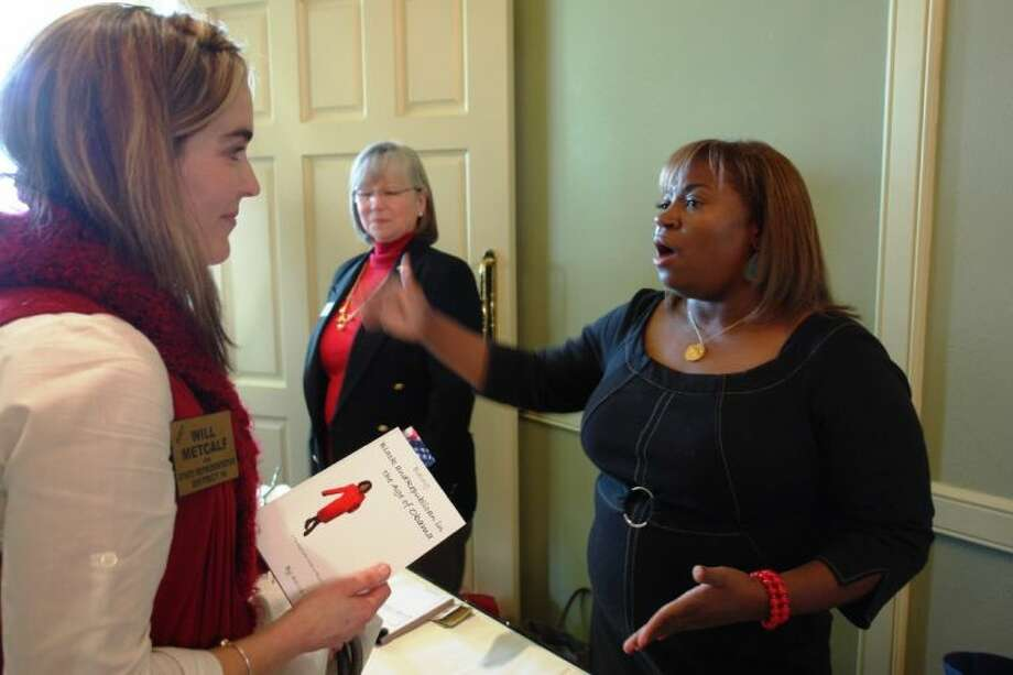 """Guest speaker Karen Watson (right) signs a copy of her book for Megan Metcalf at Wednesday's North Shore Republican Women meeting. Watson is the author of """"Being Black and Republican in the Age of Obama."""""""