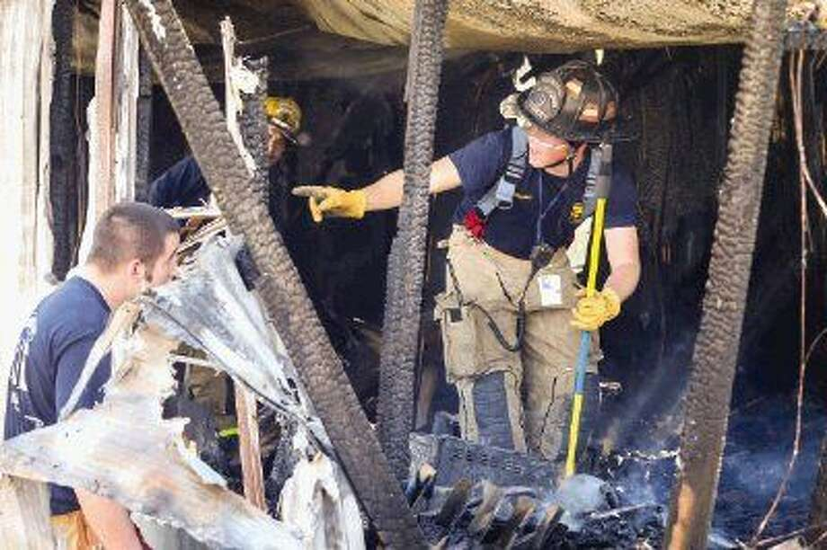 North Montgomery County firefighters respond to a mobile home fire on Monday, Feb. 9, 2015, in Willis, where a dead body was found after the fire was contained. Photo: Michael Minasi