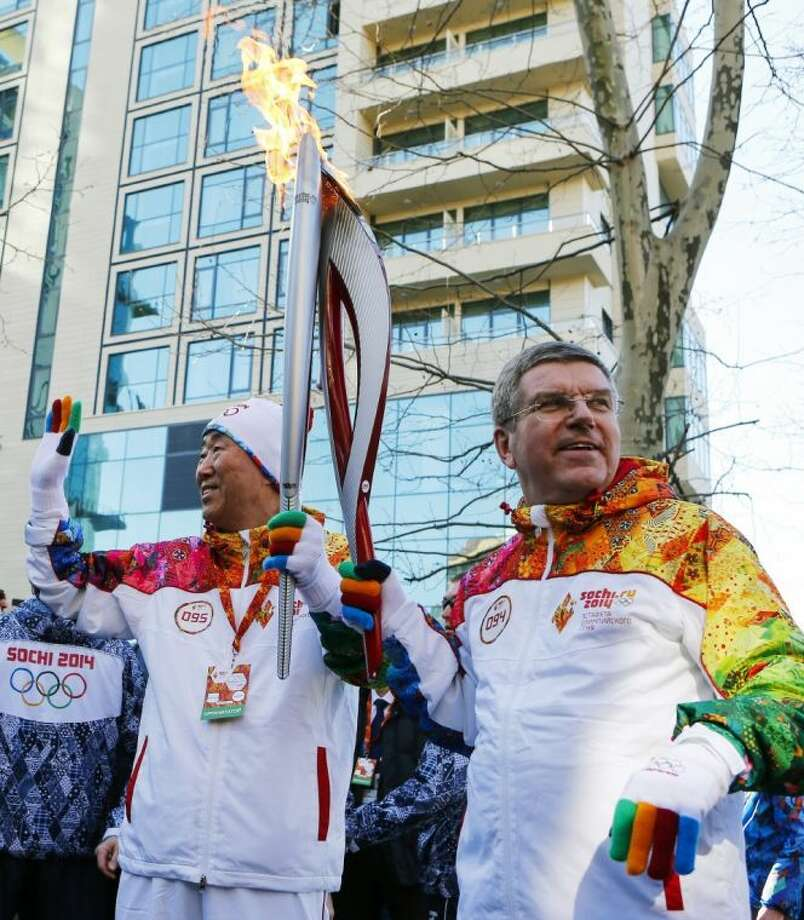 IOC President Thomas Bach, right, hands over the Olympic torch to United Nations Secretary-General Ban Ki-moon as the torch relay arrives in Sochi, ahead of the 2014 Winter Olympics, Thursday in Russia. Photo: Shamil Zhumatov