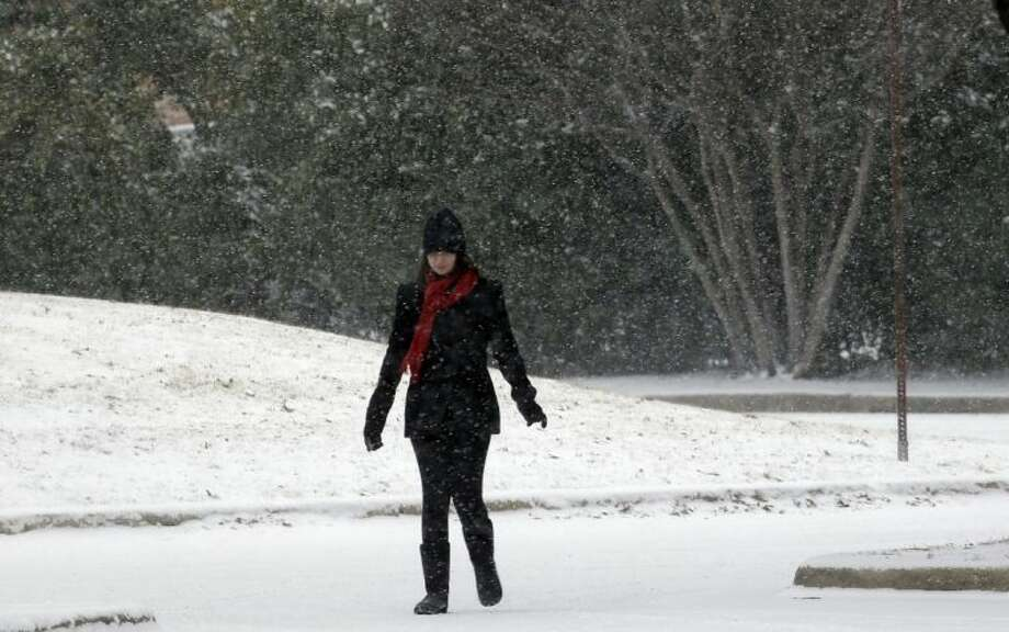 A pedestrian makes her way as snow falls in the Dallas suburb of Richardson Thursday. Photo: LM Otero