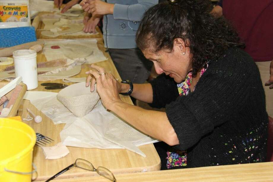 Dr. Lourdes Flanagan, a member of The John Cooper School Fine Arts Council, was among the parents, faculty and staff who learned how to make bowls for the school's annual Empty Bowls event on Feb. 20.