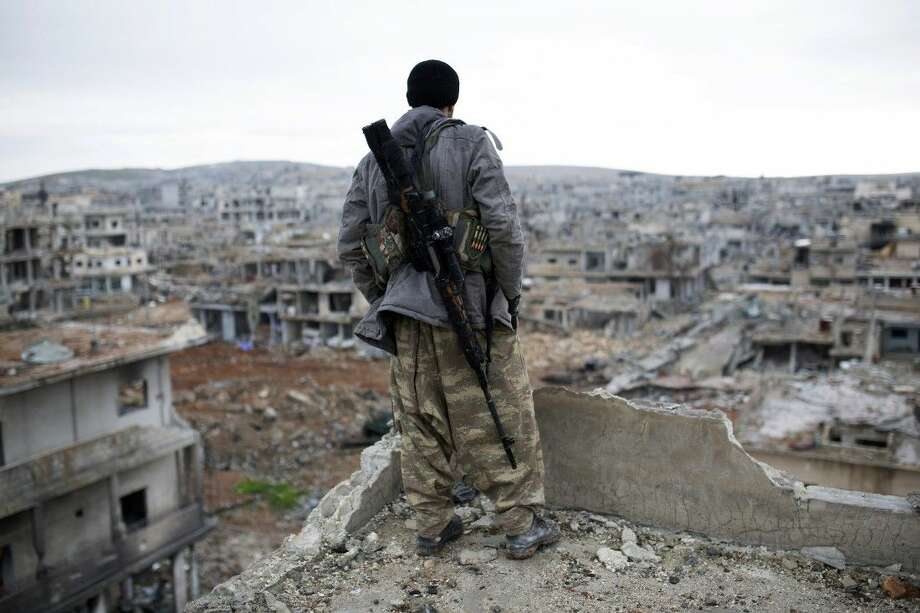 A Syrian Kurdish sniper looks at the rubble Jan. 30 in the Syrian city of Ain al-Arab, also known as Kobani. Foreign fighters are streaming in unprecedented numbers to Syria and Iraq to battle for the Islamic State or other U.S. foes, including at least 3,400 from Western nations and 150 Americans, U.S. intelligence officials conclude. Photo: Uncredited