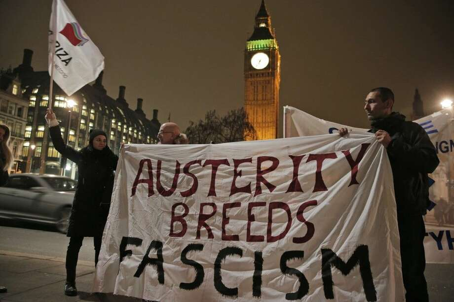 With London's Houses of Parliament in the background, protesters on Wednesday hold a banner at a rally to show solidarity with Greece. Photo: Lefteris Pitarakis