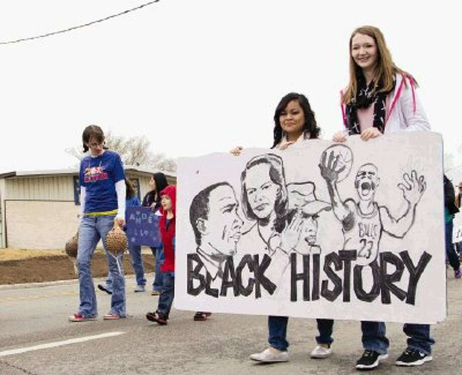 """Two girls hold a sign made by Anderson Elementary minutes before The J-Mac 56th Annual Black History Parade kicked off in downtown Conroe on Saturday. The parade was officially named the J-Mac Annual Black History Parade after organizers honored radio personality James Garrett, also known as J-Mac on 97.9 FM """"The Box."""" To view or purchase this photo and others like it, visit HCNpics.com. Photo: Staff Photo By Ana Ramirez / The Conroe Courier/ The Woodland"""