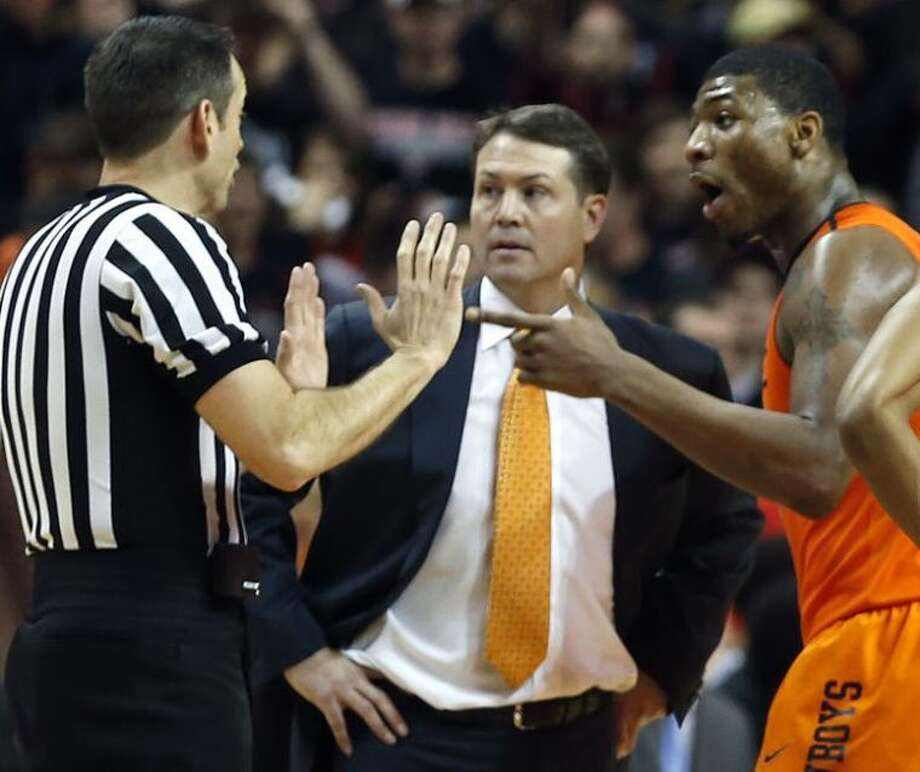 Oklahoma State's Marcus Smart, right, was suspended for three games after an incident with a fan on Saturday night at Texas Tech. At center is OSU coach Travis Ford. Photo: Tori Eichberger