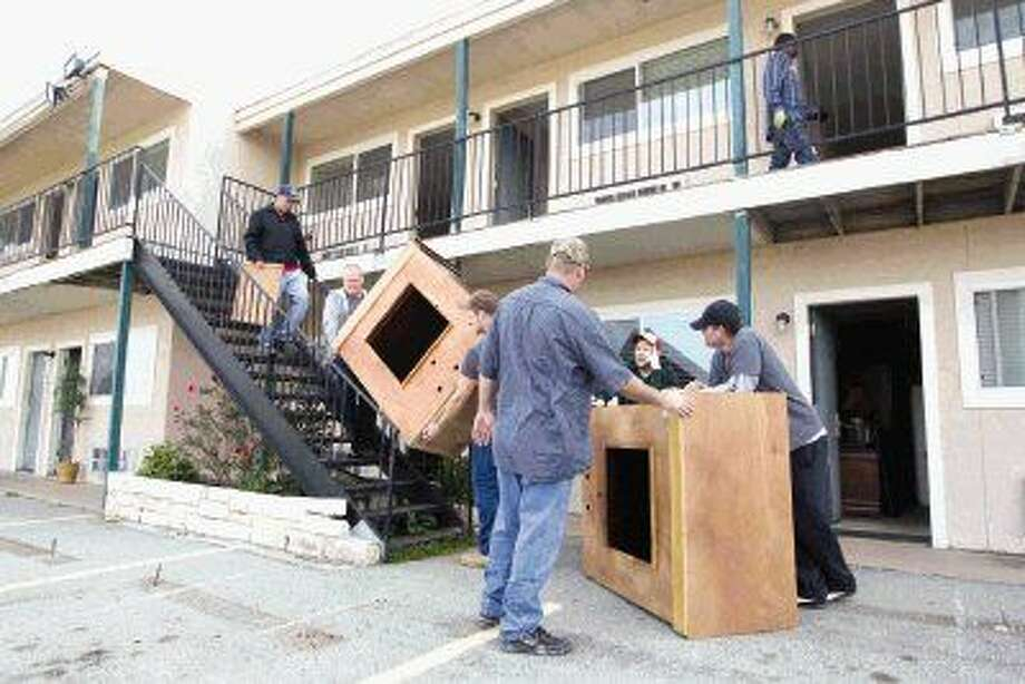 Men from Helping Hands Ranch in Willis on Thursday packed up more than 100 pieces of furniture from the April Plaza Marina and Motel to go to Montgomery County Emergency Assistance. Photo: Jason Fochtman