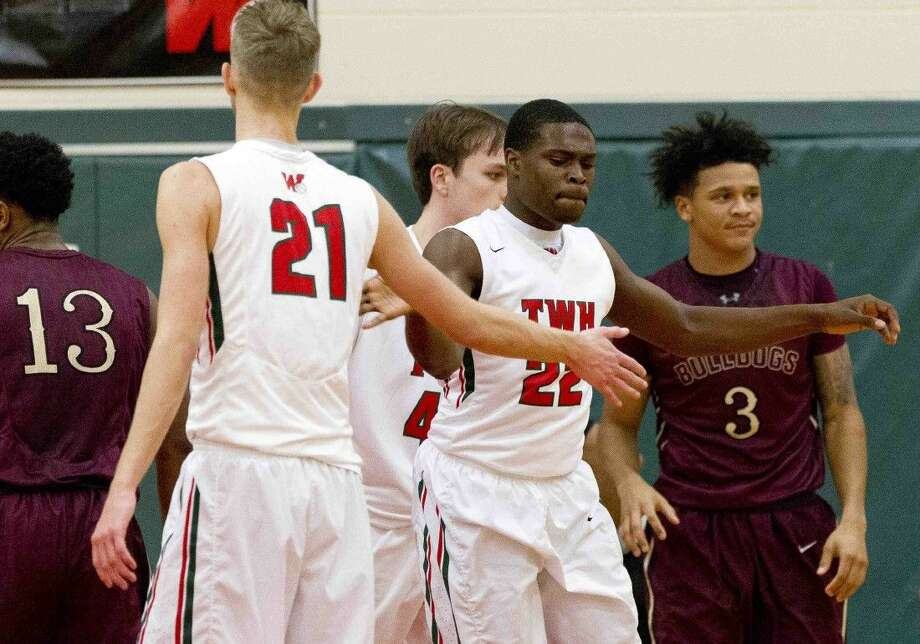 The Woodlands small forward Romello Wilbert gives a high-five to The Woodlands small forward A.J. Bullard after drawing a foul during the second quarter of a District 16-6A boys basketball game Tuesday. Photo: Jason Fochtman