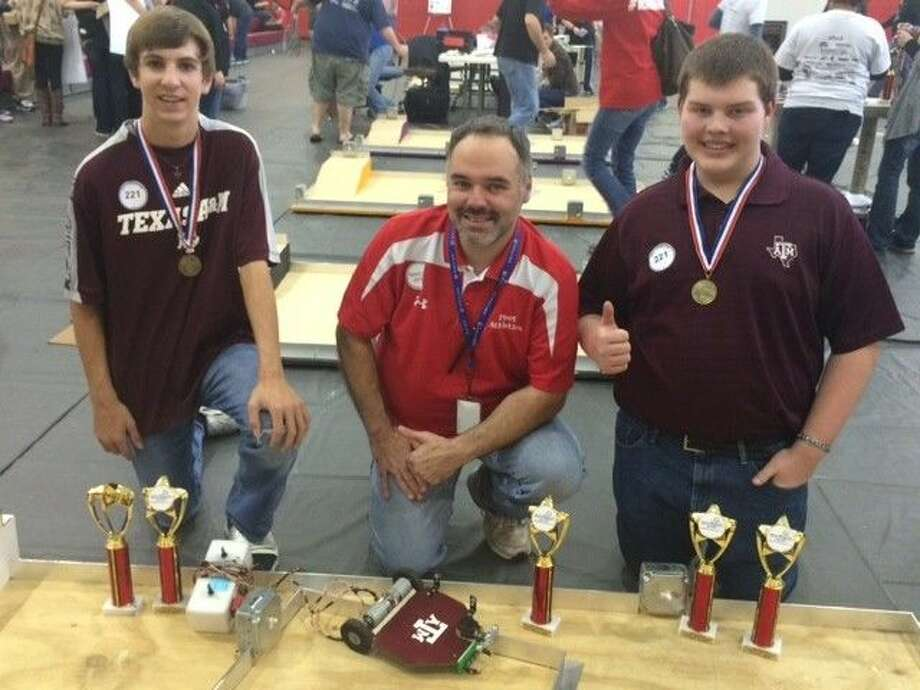 Cody Pursifull, left, and Kyle Mrosko, right, with teacher Jeffrey Fletcher after winning a robotics competition Feb. 7 at Moorhead Junior High School. Both students plan on attending Texas A&M University to study engineering.