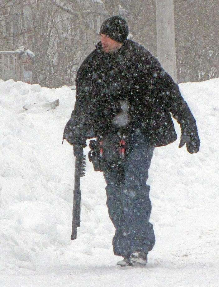 Police search during a snowstorm Friday for a suspect in a foiled attack in Cole Harbour, a suburb of Halifax, Nova Scotia. Photo: Darrell Oake