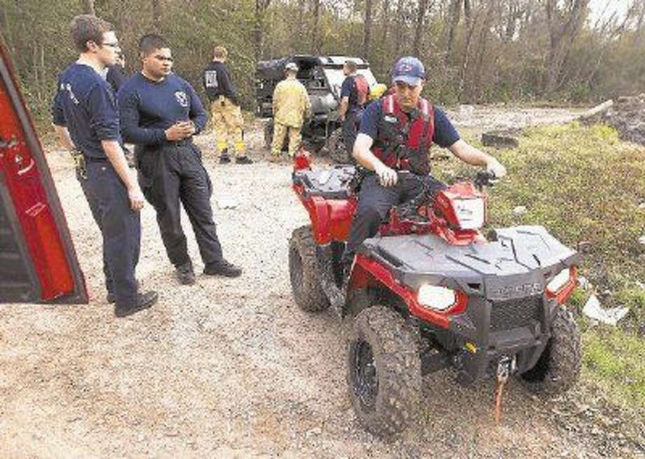 Members of The Woodlands Fire Department load up on ATVs to ride to a section of the San Jacinto River in search of a body near F.M. 1488 and I-45 on Thursday.
