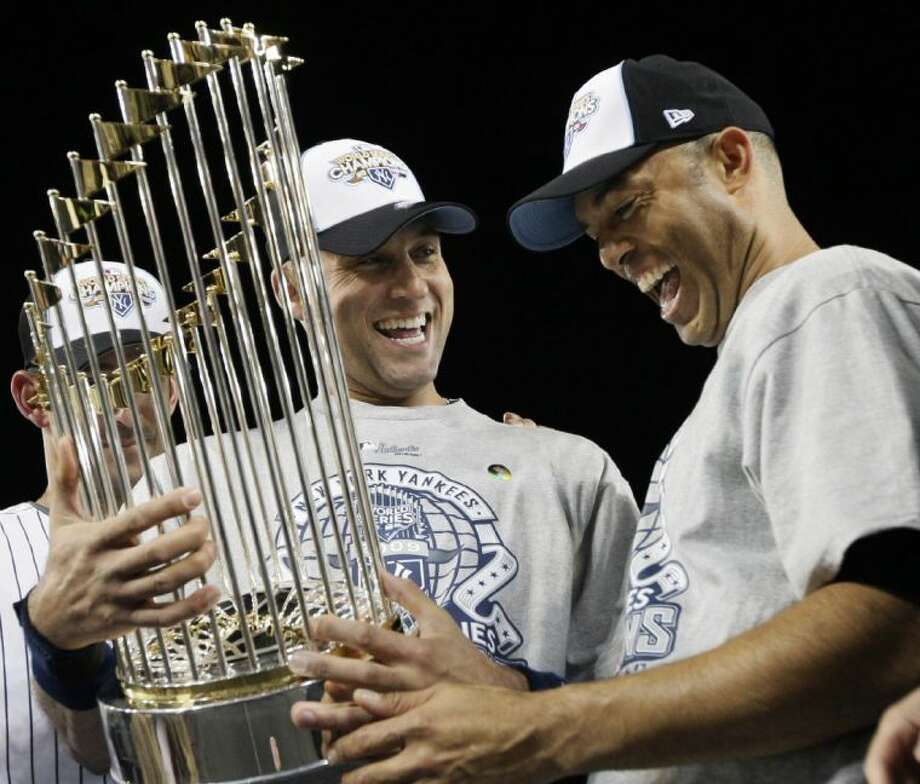 New York Yankees shortstop Derek Jeter, left, and Mariano Rivera look at the championship trophy after winning the World Series against the Philadelphia Phillies on Nov. 4, 2009, in New York. Photo: David J. Phillip