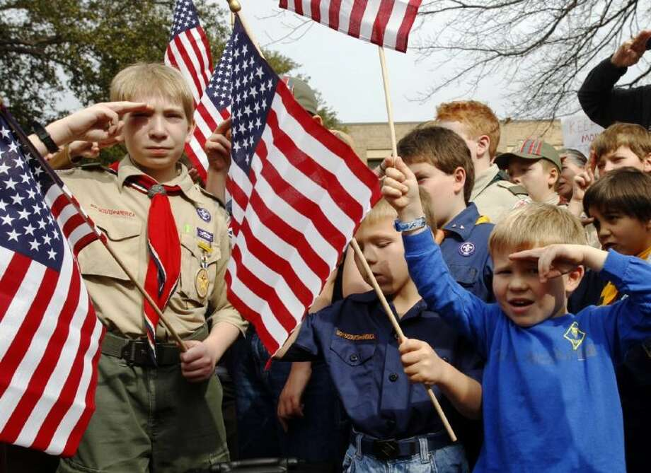 """In this Feb. 6, 2013 file photo, from left, Joshua Kusterer, 12, Nach Mitschke, 6, and Wyatt Mitschke, 4, salute as they recite the pledge of allegiance during the """"Save Our Scouts"""" prayer vigil and rally against allowing gays in the organization in front of the Boy Scouts of America National Headquarters in Dallas."""