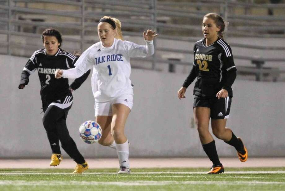 Oak Ridge midfielder Hailey Miller dribbles the ball downfield as Conroe's Kassidy Hugenschmidt (22) and Nayari Arquieta (2) give chase during a District 14-5A match on Wednesday at Woodforest Bank Stadium. To view or purchase this photo and others like it, visit HCNpics.com. Photo: Jason Fochtman