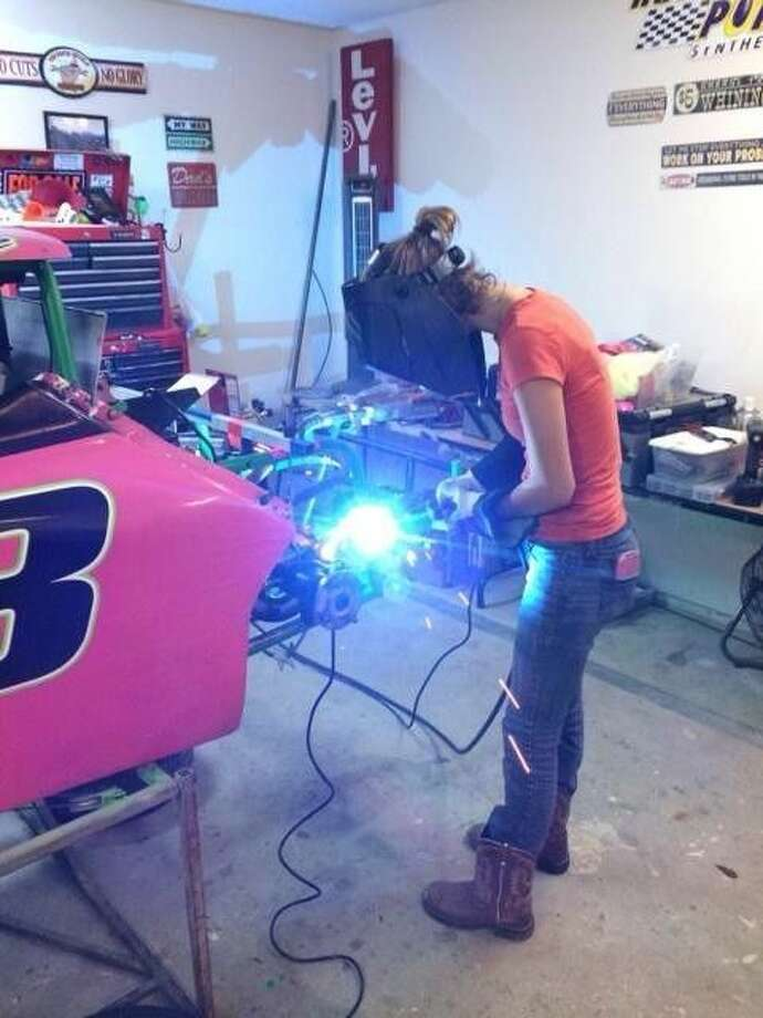 Gabbie Dubeau uses a welder on her car. Dubeau races in the Inexpensive Racing division and was the Outlaw group's top female in the nation for 2014.