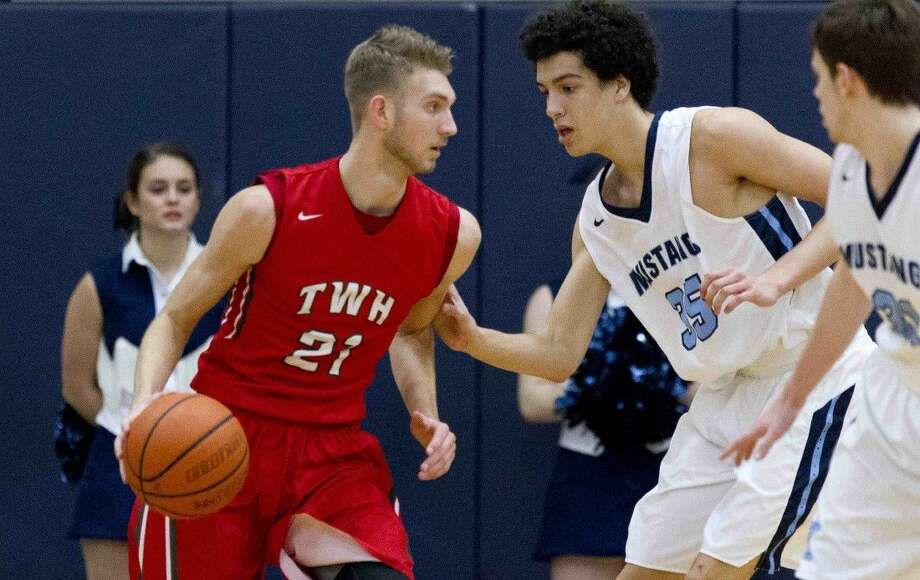 The Woodlands small forward A.J. Bullard goes up against Kingwood forward Deven Gould during a District 16-6A game Friday in Kingwood. Photo: Jason Fochtman