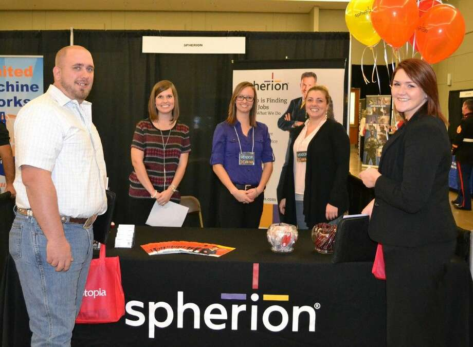 Job seekers check out the Spherion Staffing booth at the 2015 Job Fair. This year's event takes place today at the Lone Star Convention Center. More than 35 companies are on hand for the event.