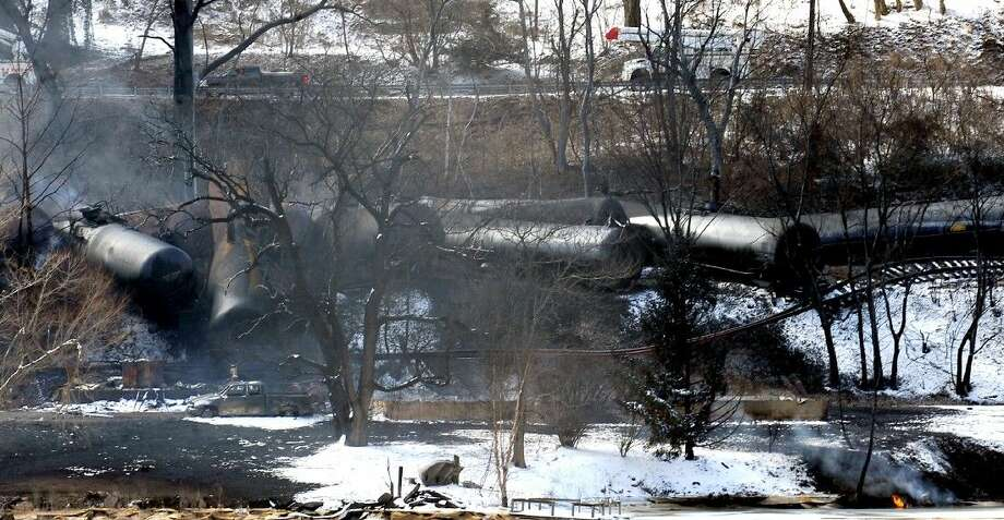 A train derailment that sent a tanker with crude oil into the Kanawha River on Monday was still smoldering Tuesday near Mount Carbon, W.Va. Photo: Chris Tilley