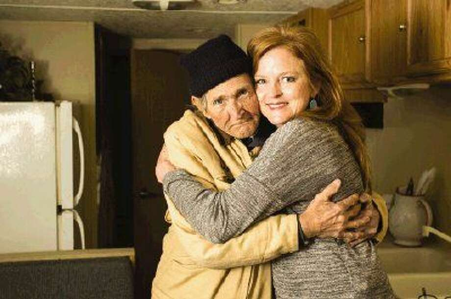 Kristin Greer, right, owner of Gilmore's Flowers and Gifts in Conroe, hugs Willy, a local homeless man, in Willy's new trailer home. Greer, who saved Willy's life by rushing him to the hospital, has helped raised funds and donations for the new trailer and medical bills for Willy, who has lived for the past eight years in a tent near the flower shop. Photo: Michael Minasi