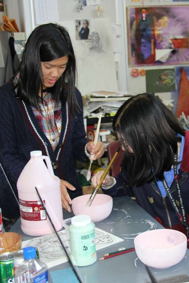 The John Cooper School seniors Meiya Cho and Haley Kent finish up some painting of a handmade bowl, which will be given away as part of the Empty Bowls Project fundraiser for the Interfaith Food Pantry on Saturday.