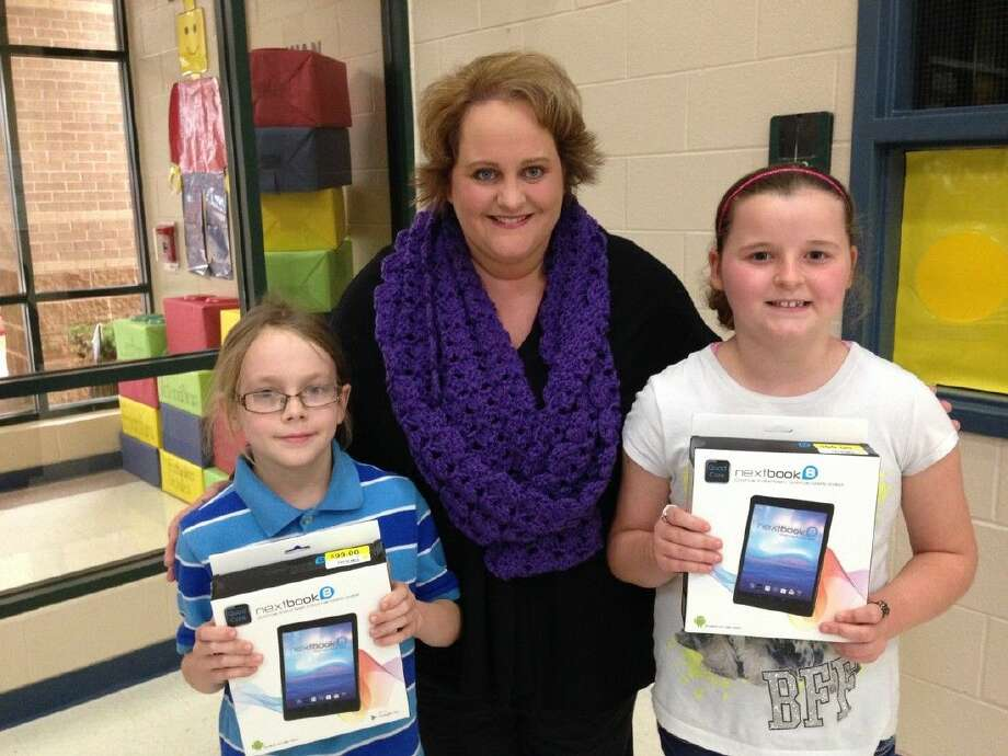 Right: Cannan Elementary School Principal Kim Sprayberry presented Jacob Downs and Faith Vickery with Nextbook tablets after their names were drawn from a pool of students with perfect attendance during the first semester.