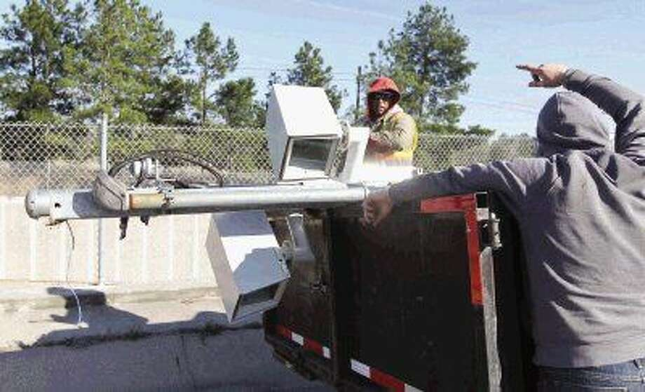 Workers remove red light cameras from the intersection of South Loop 336 and Frazier. All 10 red light cameras in Conroe were taken down this week after voters approved a proposition to repeal the authority for the cameras May 10.