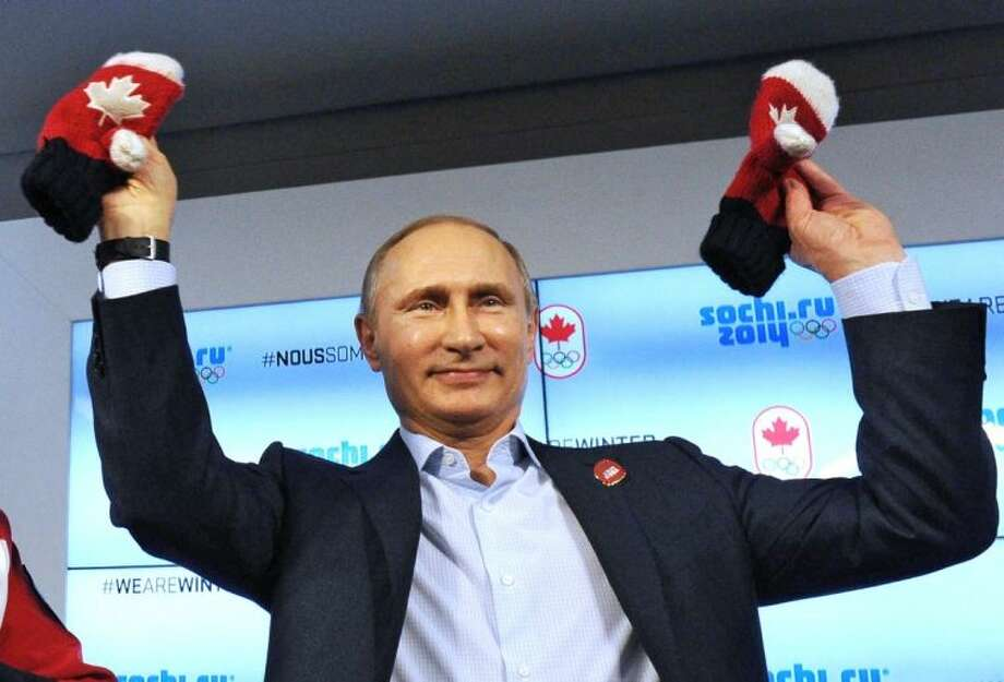 Russian President Vladimir Putin shows handmade mittens presented to him at Canada House during the 2014 Winter Olympics Friday in Sochi, Russia.