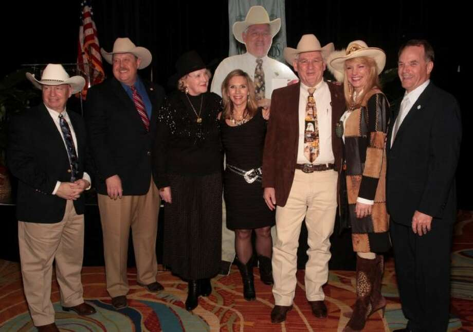 Local dignitaries surround Sheriff Tommy Gage, third from the right, both the real man and his cut out twin as the Woodlands Wine Dinner ended on February 1. The dinner honored Sheriff Gage this year.