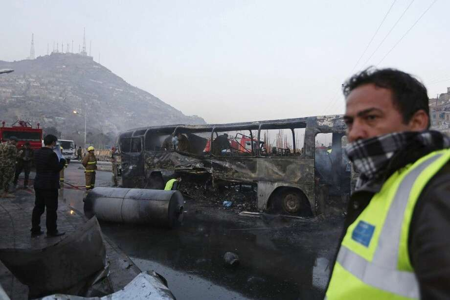 Afghan security guards on Dec. 13 inspect a damaged bus at the site of a suicide attack by the Taliban in Kabul, Afghanistan. The Afghan government is set to open a dialogue with Taliban insurgents it has been fighting for more than a decade, officials, diplomats and experts said Saturday. Photo: Rahmat Gul
