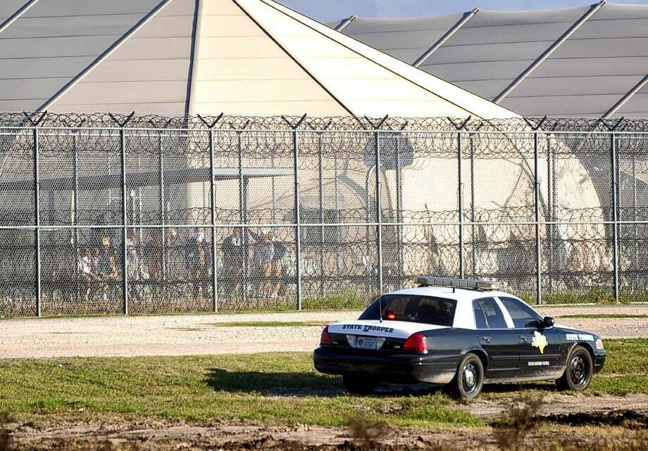 Prisoners on Friday stand at the western fence as law enforcement officials converge on the Willacy County Correctional Center in Raymondville after a prisoner uprising at the private immigration detention center. Photo: David Pike