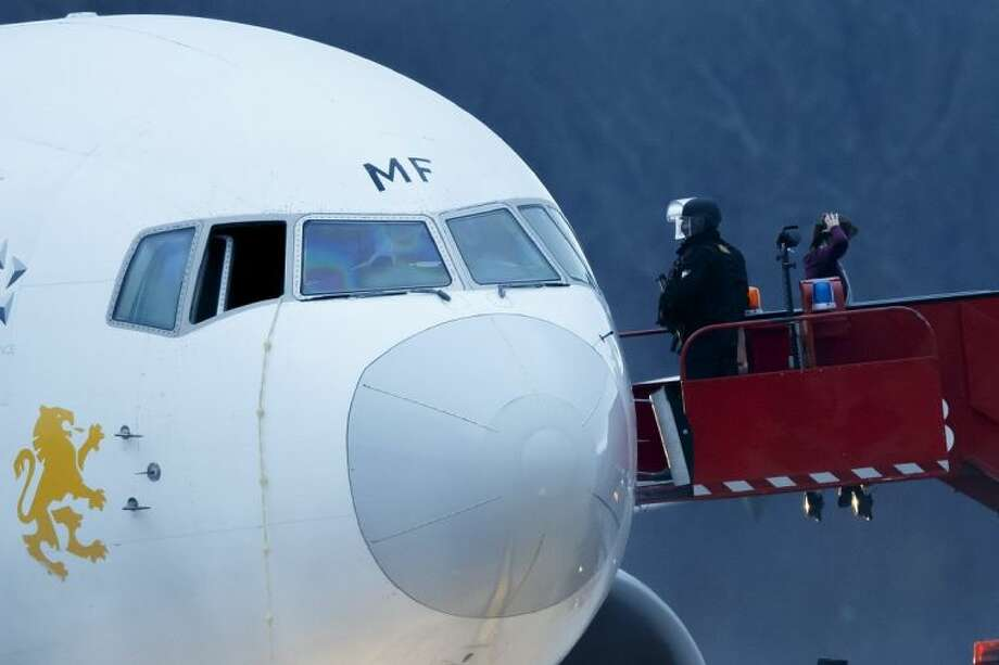 Police stand on the stairs after passengers were evacuated from a hijacked Ethiopian Airlines Plane on the airport in Geneva, Switzerland, Monday. The aircraft traveling from Addis Abeda, Ethiopia, to Rome, Italy, has landed at Geneva's international airport early Monday morning. Swiss authorities have arrested the co-pilot. Photo: Salvatore Di Nolfi